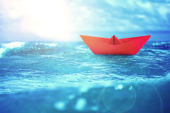 Close up sea water surface with red paper boat Royalty Free Stock Photo