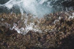 Close up sea wave crashing on the rock and make a splashing water with bubble.  stock photography
