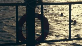 Close-up, sea waves at sunset, in the rays of soft sunlight. glare on the water. outlines of a lifebuoy that hangs on stock video footage