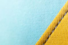 Close-up of seamded up fabrics in two pastel tones - yellow and light blue with grey seam - visible weave. Trendy decorative background with copy space for Stock Photo