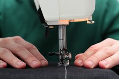 Close-up seamstress hands working on sewing machine at home. Sewing process. woman hands behind sewing close-up.  stock photography
