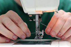 Close-up seamstress hands working on sewing machine at home. Sewing process. woman hands behind sewing close-up. The process of. Threading into the needle stock photos