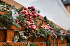 Seasonal winter decoration of artificial frosted red berries and pine branches at traditional Christmas market sales booth