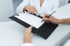 Close up. The secretary in a medical clinic helps the patient complete the necessary forms before starting treatment. stock photo