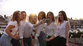Close up of a seductive, young women taking selfie outdoors on a terrace. Happy, cheerful girls in white casual clothes stock video