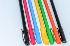 Close-up selection of Multi Colored Boll pint pens, close together in a row arrangement in white background, flat lay. Horizontal stock photo