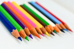 Close-up of a selection of Multi Colored pencils crayons, stick together arranged in a row line bar graph on white background, stock photography