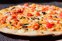 Delicious fresh pizza with tomatoes, mushrooms and cheese close up. Close up selective focus fresh tasty pizza with mushrooms and tomatoes on top royalty free stock photo