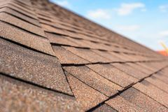 Asphalt tile roof on new home under construction. Close up and selective focus photo of asphalt shingle or tile on roof of new house under construction against royalty free stock images