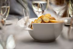 Close-up selective focus photography. On the table between the g. Lasses is a white bowl of fried potatoes Royalty Free Stock Image