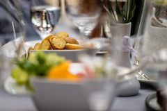 Close-up selective focus photography. On the table between the g. Lasses is a white bowl of fried potatoes Royalty Free Stock Images