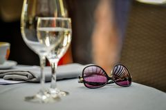 Close-up selective focus photography. On the table are sunglasse. S and wine glasses Royalty Free Stock Images