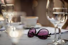 Close-up selective focus photography. On the table are sunglasse. S and wine glasses Royalty Free Stock Photography