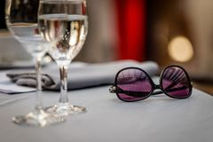 Close-up selective focus photography. On the table are sunglasse. S and wine glasses Royalty Free Stock Photo