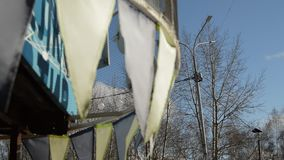 Close-up, selective focus, wind slaps garlands of colorful flags against blue sky, Park in spring.  stock video footage