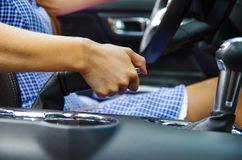 Close up of selective focus of woman s hand actioning a hand brake inside of her car, standing on the sidelines Stock Photography