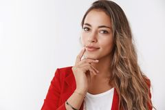 Close-up self-assured successful rich businesswoman wearing red jacket touching jawline smiling confident looking camera. Smart intelligent, know how maintain stock photography