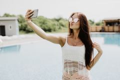 Close-up selfie-portrait of attractive brunette girl with long hair standing near pool. She wears pink T-shirt, sunglasses. Stock Image