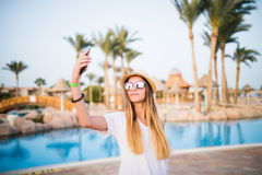 Close-up selfie-portrait of attractive girl with long hair standing near pool wears in sunglasses and hat smiling to the camera. Stock Images