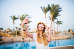 Close-up selfie-portrait of attractive girl with long hair standing near pool wears in sunglasses and hat smiling to the camera. Royalty Free Stock Photography