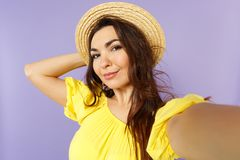 Close up selfie shot of beautiful young woman in yellow dress, summer hat putting hand on head  on pastel violet royalty free stock photos