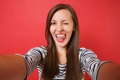 Close up selfie shot of cheerful young woman in casual striped clothes blinking, showing tongue isolated on bright red. Wall background. People sincere emotions royalty free stock images