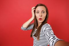 Close up selfie shot of shocked young woman in striped clothes keeping hand near head, looking amazed isolated on red stock photography