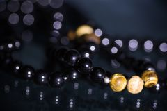 Close up of semiprecious gemstone tigers eye and black tourmaline bracelets on black background design Royalty Free Stock Photography