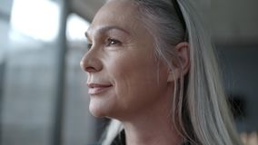 Senior business woman looking outside window. Close up of senior business woman standing in office and looking outside window. Mature business professional with stock video footage
