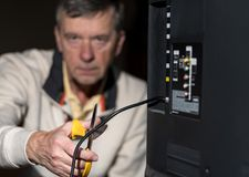 Senior man cutting the cord on his cable TV package. Close up of senior caucasian retired man cutting the aerial connection to his TV to illustrate cutting the royalty free stock photo