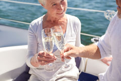 Close up of senior couple with champagne on boat. Sailing, age, travel, holidays and people concept - close up of happy senior couple drinking champagne on sail royalty free stock images
