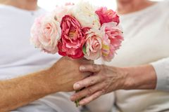 Close up of senior couple with flowers. Family, holidays, age and people concept - close up of happy senior couple hands with bunch of flowers at home stock photo