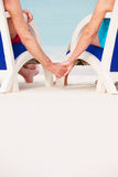Close Up Of Senior Couple Holding Hands Beach In Chairs Stock Images