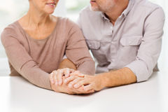 Close up of senior couple holding hands at home Stock Images