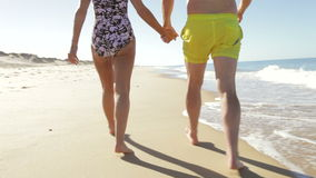 Close Up Of Senior Couple Holding Hands Walking Along Beach. Camera follows senior couple as they walk away from camera along beach holding hands.Shot on Canon stock video
