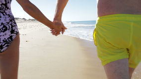 Close Up Of Senior Couple Holding Hands Walking Along Beach. Camera follows senior couple as they walk away from camera along beach holding hands.Shot on Canon stock video footage