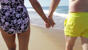 Close Up Of Senior Couple Holding Hands Walking Along Beach. Camera follows senior couple as they walk away from camera along beach holding hands.Shot on Canon stock video footage