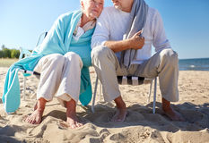 Close up of senior couple sitting on beach chairs. Family, old age, travel, tourism and people concept - close up of happy senior couple sitting on deck chairs Royalty Free Stock Images