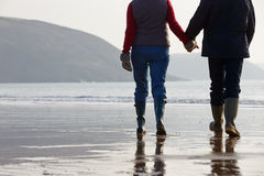 Close Up Of Senior Couple Walking Along Winter Beach Royalty Free Stock Photo