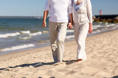 Close up of senior couple walking on summer beach Royalty Free Stock Photo