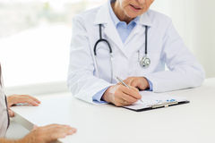 Close up of senior doctor and patient at hospital. Medicine, age, health care and people concept - close up of senior female doctor with clipboard and patient at stock images