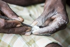 Close up of senior indian asian man sculptor carver hands working on his marble sculpture with chisel. Royalty Free Stock Image