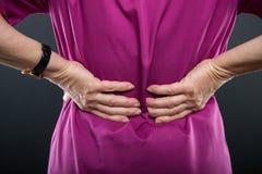 Close-up of senior lady doctor holding back like hurting. On black background Stock Photos