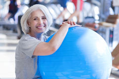 Close-up of senior lady with fitness ball. I enjoy fitness. Close up portrait of happy senior woman sitting and hugging fitness ball while having rest at gym Stock Photography