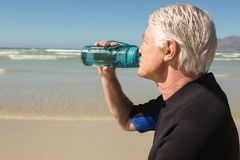Close up of senior man drinking water. At beach Stock Image
