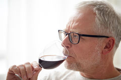 Close up of senior man drinking wine from glass. People, alcohol and drinks concept - close up of senior man drinking red wine from glass at home Royalty Free Stock Image