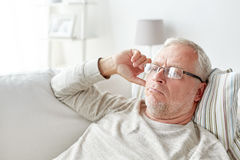Close up of senior man in glasses thinking at home Royalty Free Stock Images