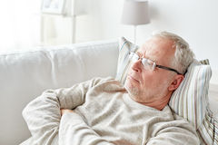 Close up of senior man in glasses thinking at home Royalty Free Stock Photo
