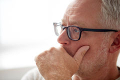 Close up of senior man in glasses thinking Stock Image