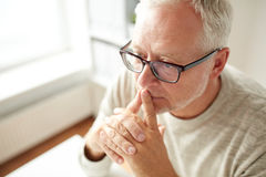 Close up of senior man in glasses thinking Royalty Free Stock Photos